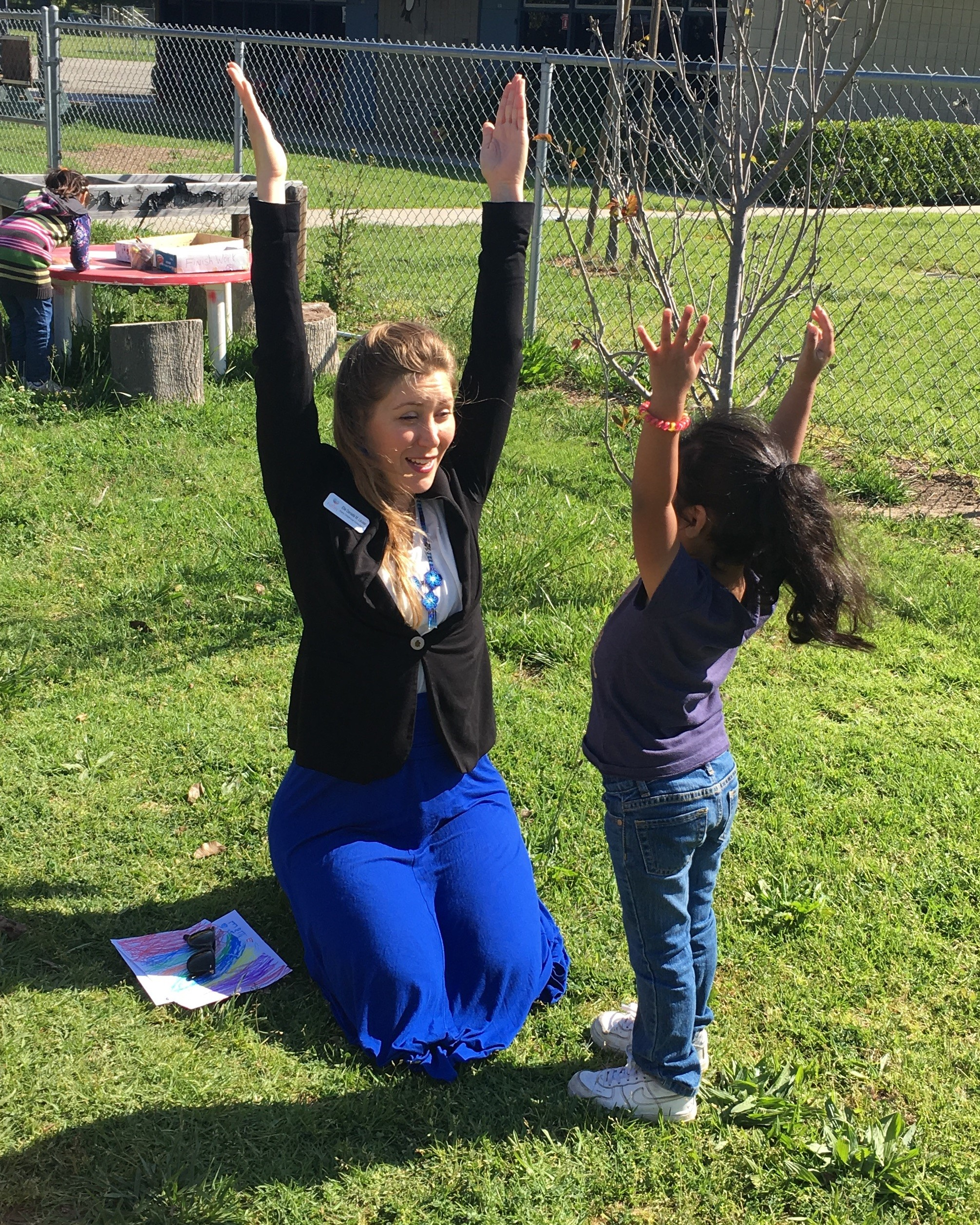 Counselor and girl with arms raised to the sky