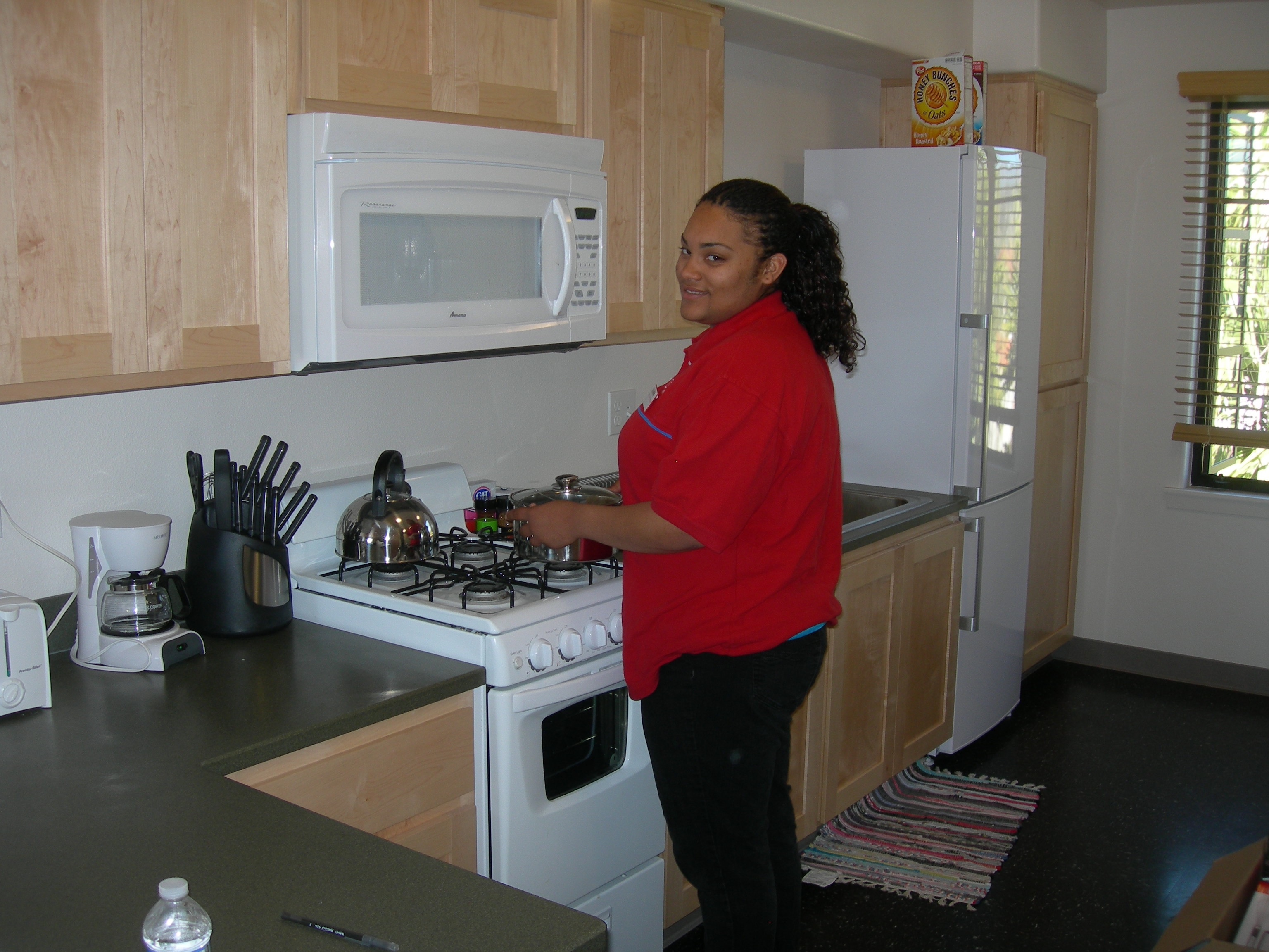 2010 Channel Islands YFS girl in red sweater in kitchenette