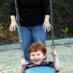 CASA Woman with child in playground swing