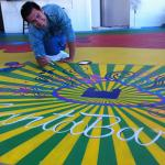 Youth Interactive: young artist painting sunburst on floor